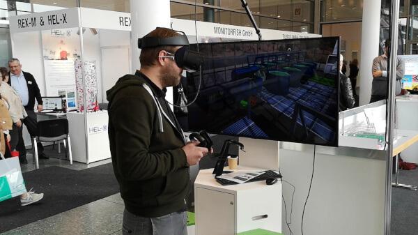 Messebesucher mit einer Virtual Reality Brille und Controllern. für die Interaktion mit einer Aquaponik Anlage